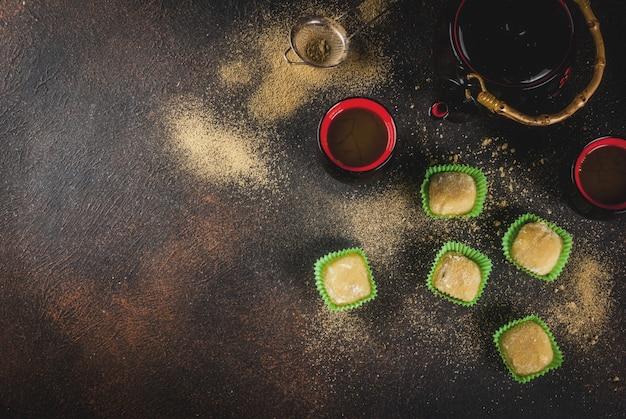 Matchathee met groene mochi, donkere roestige achtergrond. copyspace bovenaanzicht