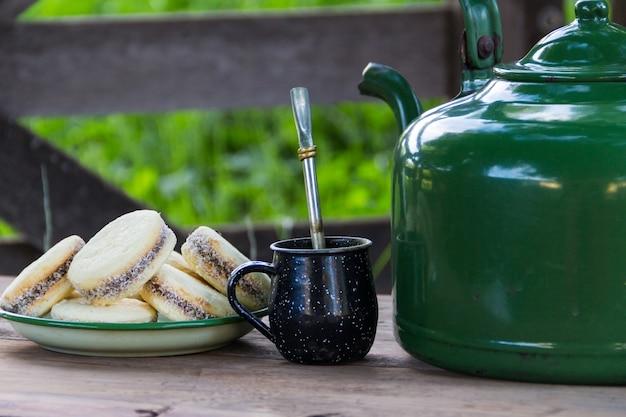 Mate en ketel met een bord alfajores en yerba mate-infusie op het argentijnse platteland