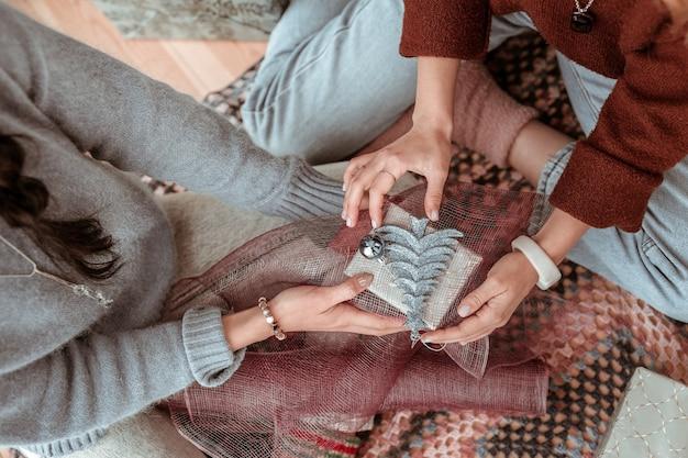 Materialen voor verpakking. nauwkeurig geïnspireerde dames die elkaar helpen met inpakken terwijl ze details aanbrengen op het kerstconcept van de doos