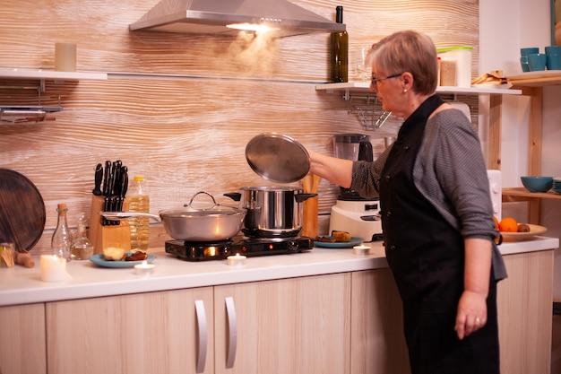 Matue-vrouw die voedsel controleert terwijl ze het kookt voor het avondeten met een oudere echtgenoot. gepensioneerde vrouw die voedzaam voedsel kookt voor haar en de man om de verjaardag van de relatie te vieren.