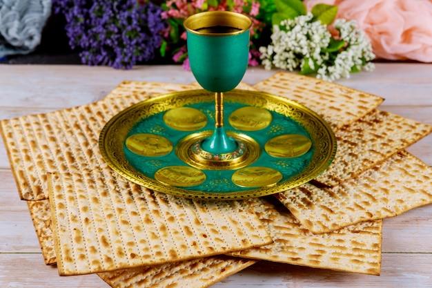 Matzah, kiddush wijn en seder met tekst in hebreeuws ei, beenkruiden, karpas chazeret en charoset. pascha concept.