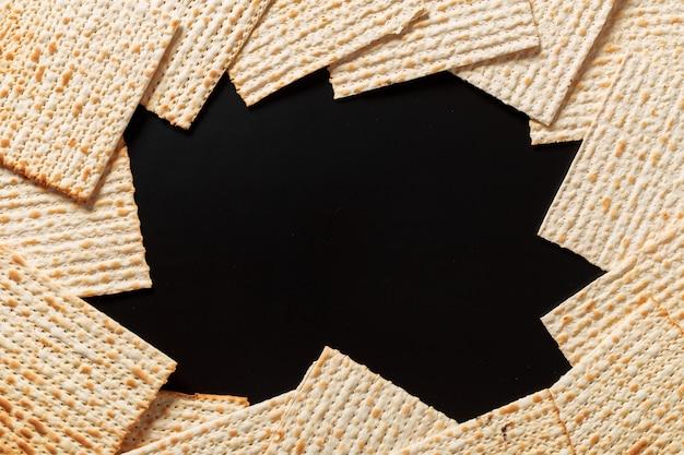 Matzah of matzo-stukken op zwart. matzah voor de joodse paschavakantie.