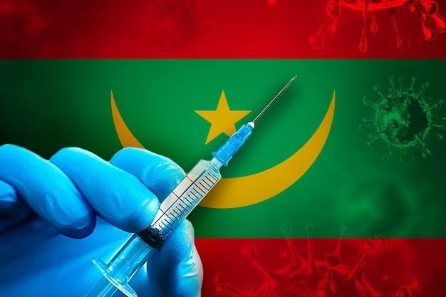 Mauritanië covid19 vaccinatiecampagne hand in een blauwe rubberen handschoen houdt de spuit voor de vlag