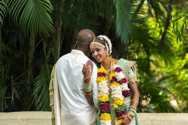 Mauritius. de bruid en bruidegom in nationale mauritiaanse outfits in de botanische tuin op het eiland mauritius.