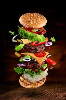 Maxi hamburger, dubbele cheeseburger met vliegende ingrediënten geïsoleerd op houten