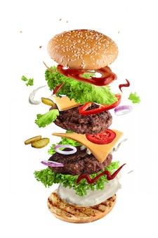 Maxi hamburger, dubbele cheeseburger met vliegende ingrediënten op wit wordt geïsoleerd