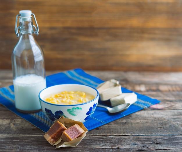 Mazamorra beker en melkfles op rustieke houten voet. latijns eten concept. kopieer ruimte.