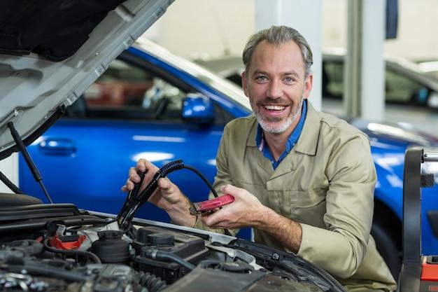 Mechanic bevestigen van startkabels om auto-accu