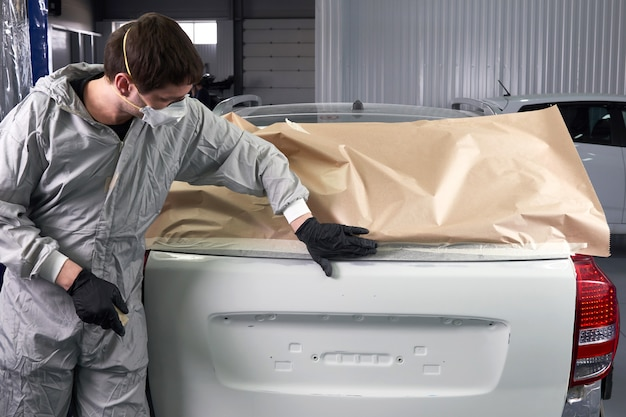 Mechanic die auto met document behandelen alvorens in de autoreparatiedienst te schilderen