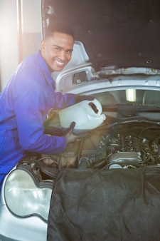 Mechanic gieten olie smeermiddel in de motor van de auto