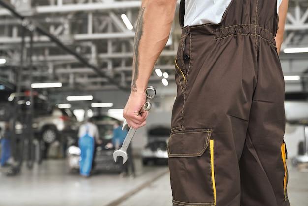 Mechanic in overall die moersleutel houden, die in autoservice stellen.