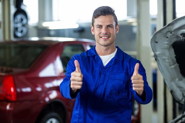 Mechanic standing in reparatiewerkplaats zien thumbs up