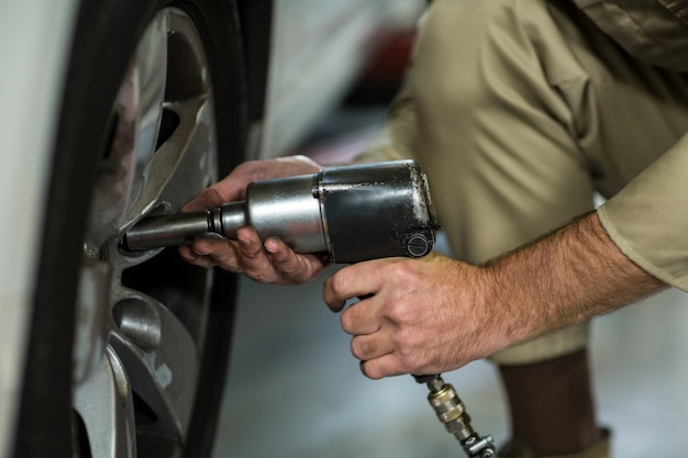 Mechanic vaststelling van een auto wiel met pneumatische moersleutel