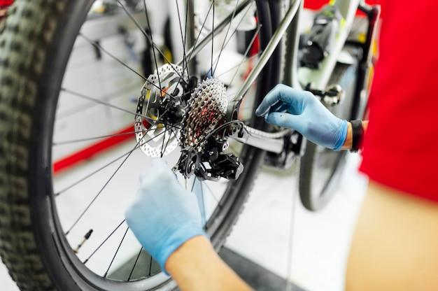 Mechanica die de fiets in de workshop bevestigen