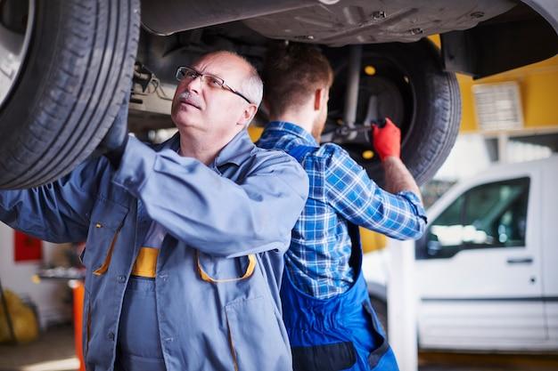Mechanica die een auto in de werkplaats herstelt