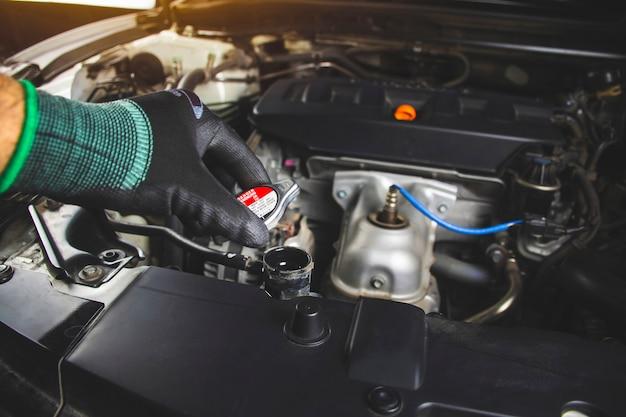 Mechanica man opent radiatordop van automotor