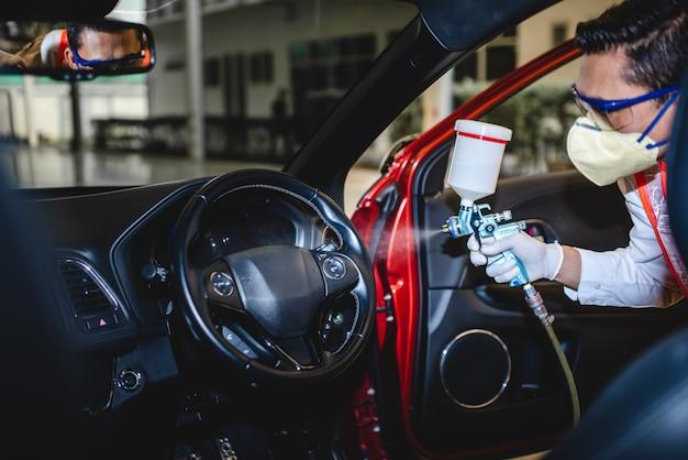 Mechanisch spuiten om de covid-19 in de auto te doden die het virus in de auto kan doden. mechanic die een beschermend masker draagt en aërosol of virus in de auto bespuit.