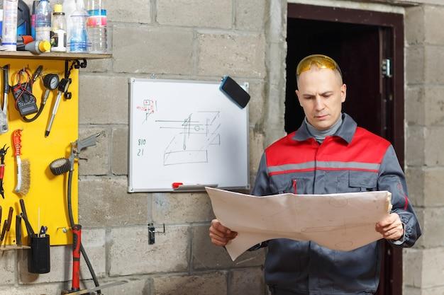 Mechanische arbeider die zijn instructies bij een bouwhuis bestudeert