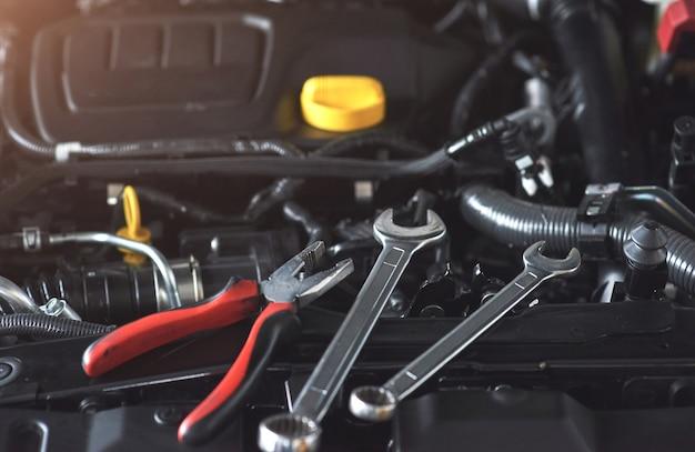 Mechanische hand controleren en repareren van een kapotte auto in de garage van de auto-service.