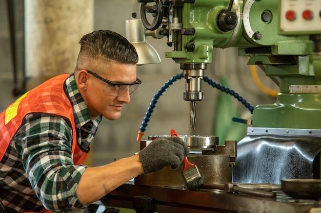 Mechanische ingenieur dragen van veiligheidsharnas gebruik freesmachine in werkplaats.
