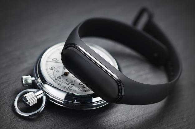 Mechanische stopwatch en fitness- of activiteitstracker op zwarte steen. sport trainingsconcept