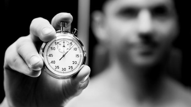 Mechanische stopwatch in een hand. mensenatleet met een wijzerplaat. fitness- en sportconcept