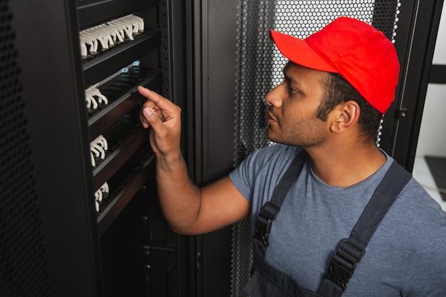 Mechanische uitdagingen. geconcentreerde it-engineer die de server onderzoekt en in profiel poseert