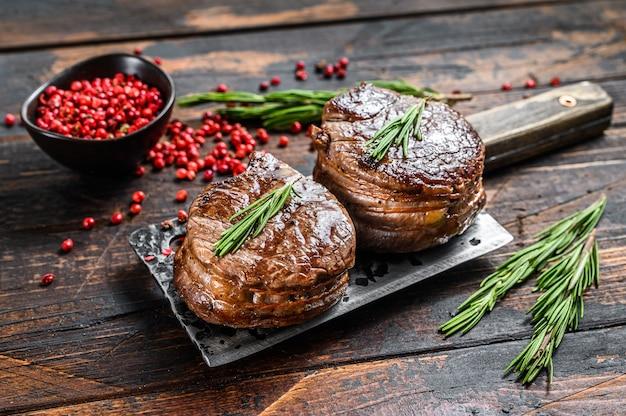 Medaillons steaks van de ossenhaas. donkere houten achtergrond. bovenaanzicht.