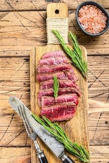 Medaillons steaks van de ossenhaas op een snijplank. houten achtergrond. bovenaanzicht.