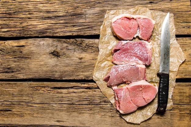 Medaillons van vers rauw vlees en het vleesmes. op houten tafel. vrije ruimte voor tekst. bovenaanzicht