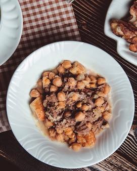 Medelijden in een witte plaat met lamsvlees, dik lamsvlees, kastanjes en erwten