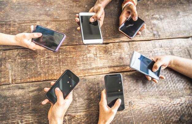 Medewerker die gebruikend mobiele slimme telefoon op houten achtergrond hebben