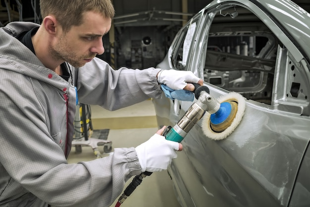 Medewerker van de carrosserie-lakwinkel polijst het geverfde oppervlak met een pneumatische polijstmachine