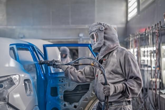 Medewerker van de carrosserie-schilderwinkel voert het schilderen uit.