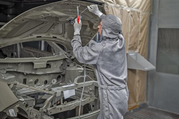 Medewerker van de spuiterij bereidt de carrosserie voor op het schilderen.