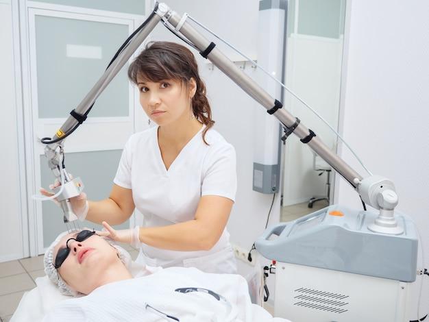Medewerker van de vrouw van de medische salon gebruikt effectieve neodymiumlaser die ongewenste littekens op het gezicht van de jonge patiënt verwijdert