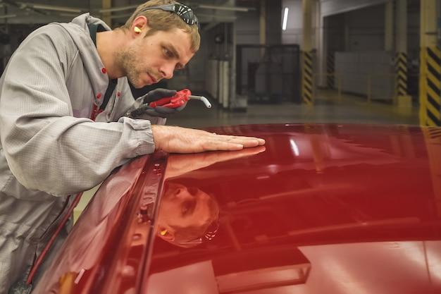 Medewerker van een autofabriek controleert de kwaliteit van de lak