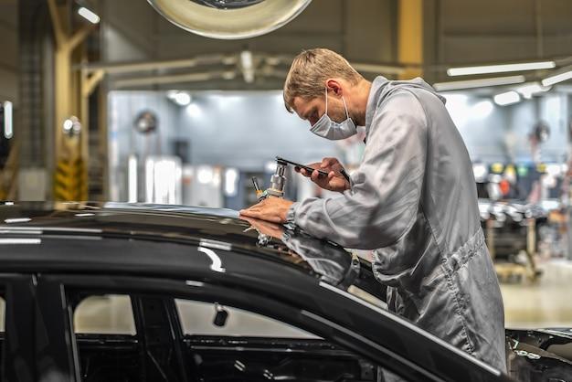 Medewerker van een autofabriek controleert de kwaliteit van het schilderen met een microscoop