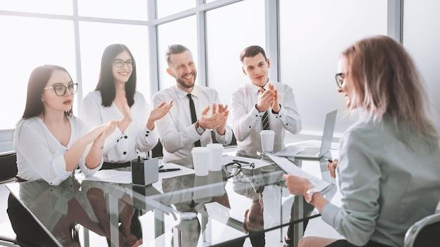 Medewerkers applaudisseerden tijdens een werkvergadering op kantoor. concept van succes