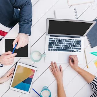 Medewerkers die apparaten gebruiken bij bureau