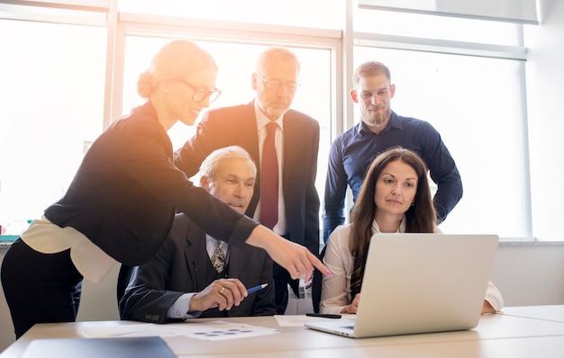 Medewerkers die een computer bekijken en over het werk in het bureau spreken