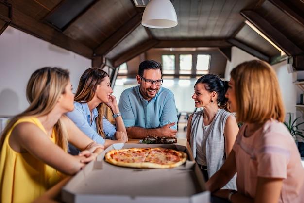 Medewerkers die pizza eten tijdens het werkonderbreking op modern kantoor.