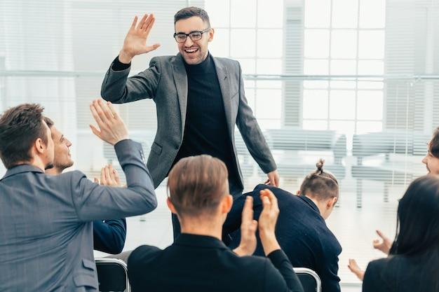 Medewerkers geven elkaar een high five tijdens een werkoverleg. concept van succes