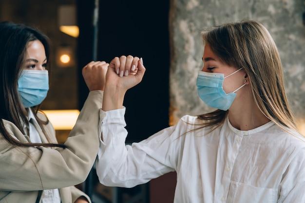 Medewerkers in beschermende maskers geven high five met ellebogen op kantoor. vrouwen werken tijdens het coronavirus