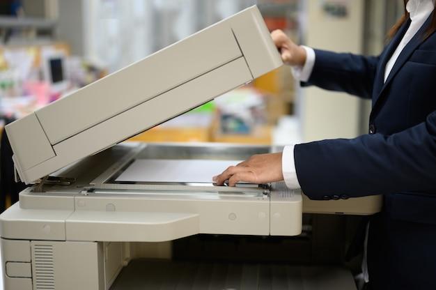 Medewerkers kopiëren documenten met een kopieermachine op kantoor.