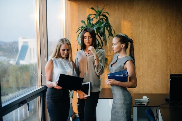 Medewerkers op kantoor om zakelijke aangelegenheden naast het raam te bespreken. bedrijfsfinanciering