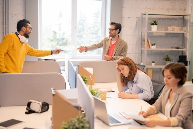 Medewerkers van de analytische afdeling die werken in een open ruimte kantoor: man uit het midden-oosten geeft papier door aan collega terwijl vrouwen documenten onderzoeken