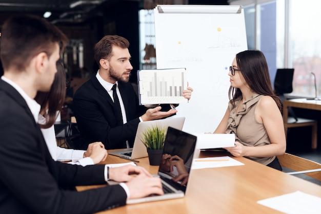 Medewerkers van het bedrijf houden een vergadering aan tafel.