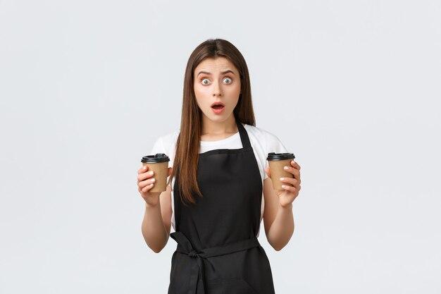 Medewerkers van supermarkten, kleine bedrijven en coffeeshops concept. bezorgde jonge vrouwelijke barista maakte een verkeerde bestelling, hield twee kopjes drankjes vast en hijgde geschokt, witte achtergrond.