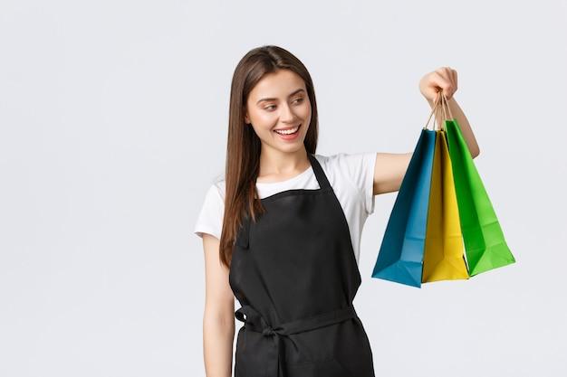 Medewerkers van supermarkten, kleine bedrijven en coffeeshops concept. mooie glimlachende verkoopster die gekochte artikelen verpakt in schattige kleurrijke papieren zakken en de bestelling overhandigt terwijl ze als kassier werkt